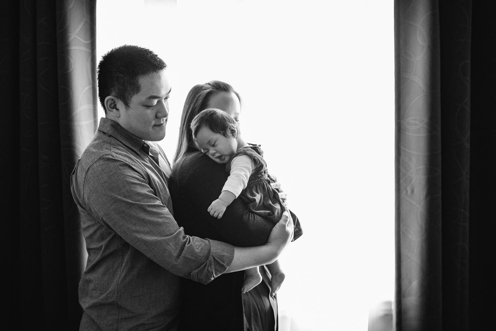 family of three standing at window, mom holding 3 month old baby girl, dad looking at his daughter - Newmarket In-Home Photos