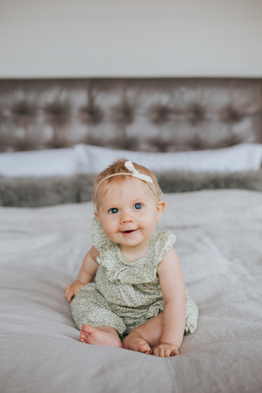 6 month old baby girl with blonde hair and blue eyes sitting on bed smiling - Newmarket In-home Family Photography