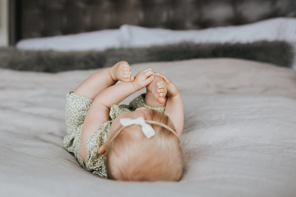 6 month old baby girl with blonde hair lying on bed playing with feet - Stouffville In-home Family Photography