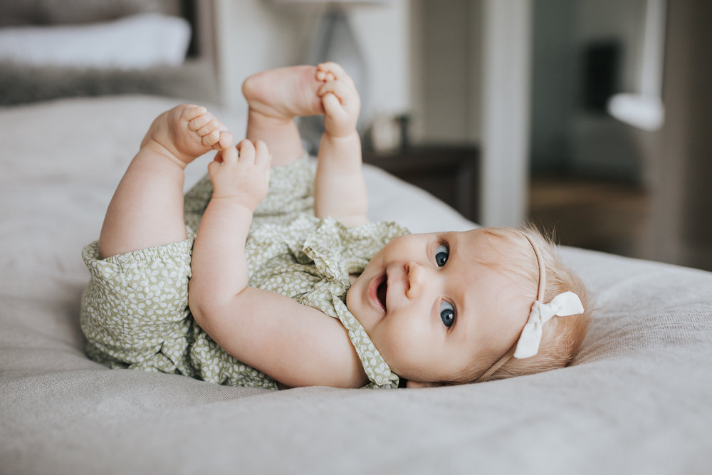 6 month old baby girl with blonde hair and blue eyes lying on bed playing with feet and looking at camera - Markham In-home Family Photography