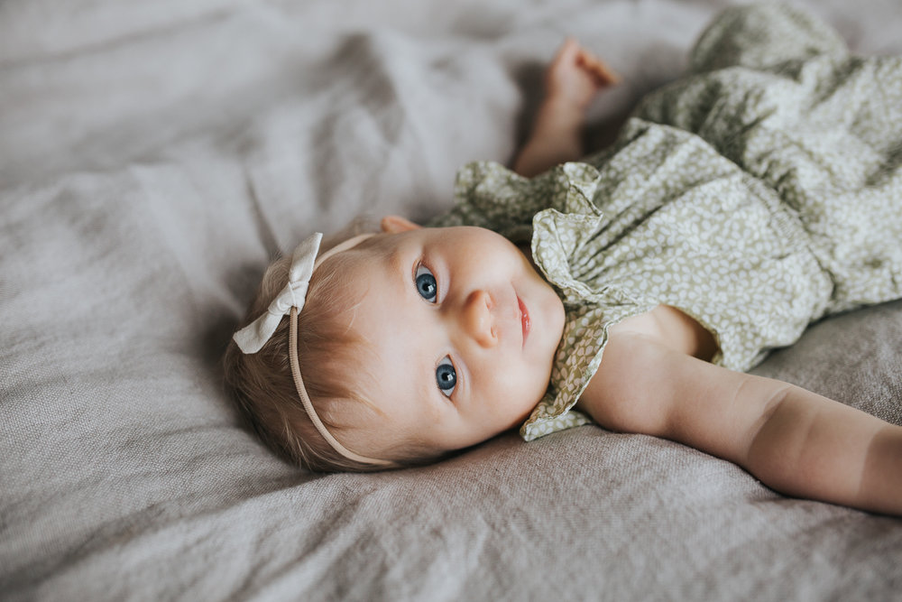 6 month old baby girl with blonde hair and blue eyes lying on bed looking at camera - Markham In-home Family Photos