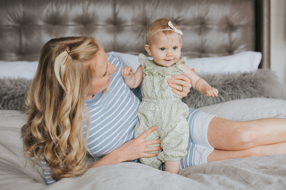 mom and 6 month old baby girl lying on bed, mother looking at daughter - Newmarket Lifestyle Family Photos