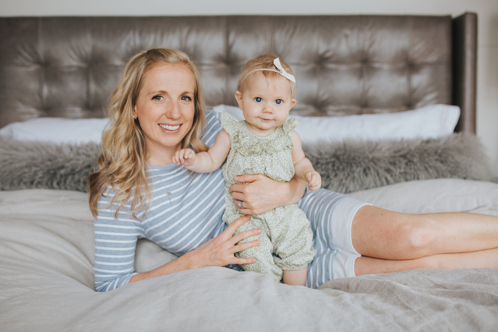 mom and 6 month old baby girl lying on bed looking at camera - Stouffville Lifestyle Family Photos