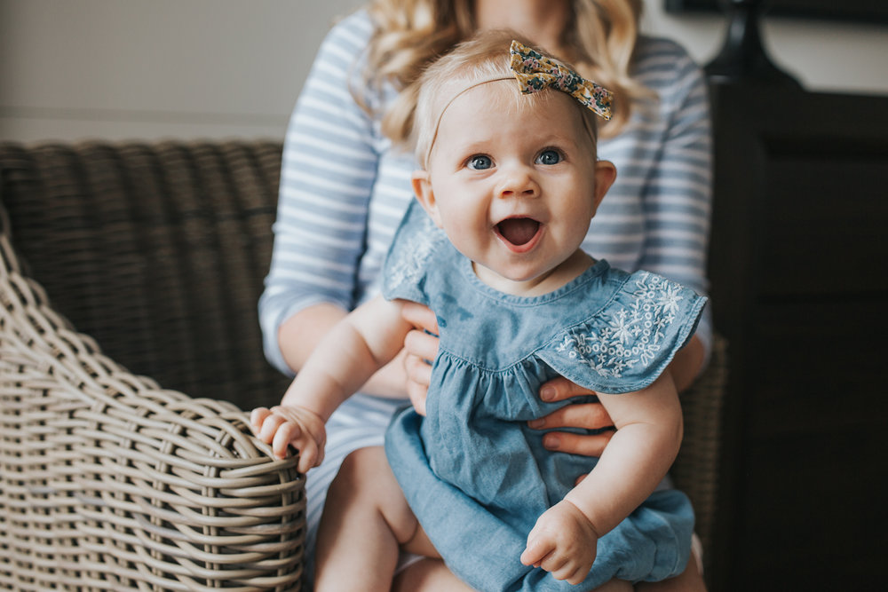 6 month old baby girl in blue dress sitting on mom's lap laughing - Barrie Lifestyle Family Photos