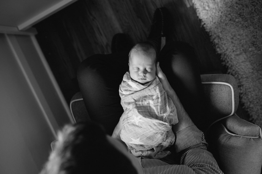 shot from above of baby girl in grey swaddle lying in her father's lap - Barrie Lifestyle Photography