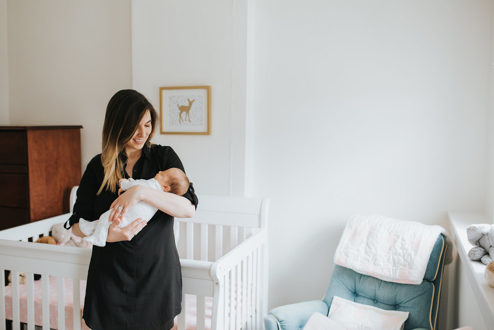 new mom holds 4 week old baby daughter standing in front of crib in pink and gold nursery - Stouffville Lifestyle Photos