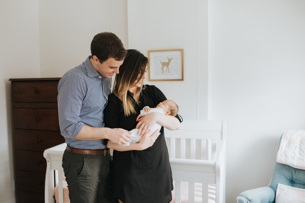 new parents hold 4 week old baby girl standing in front of crib in pink and gold nursery - Newmarket Lifestyle Photography