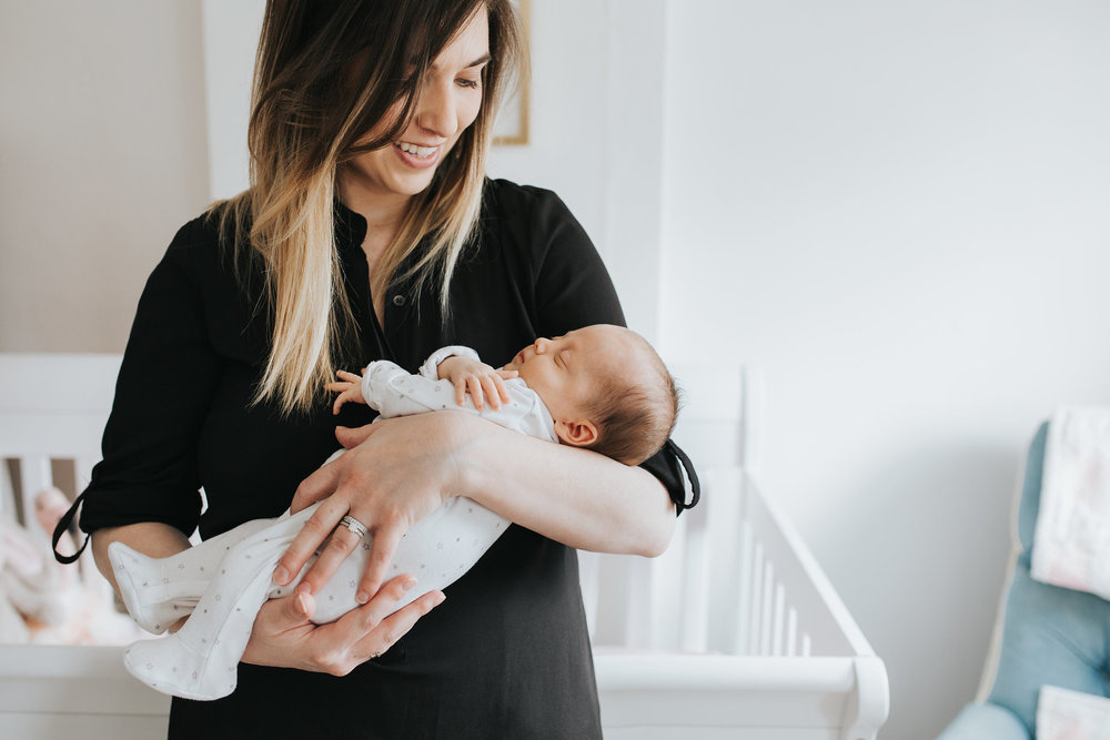 new mom holds 4 week old baby daughter standing in front of crib in pink and gold nursery - Barrie Lifestyle Photos