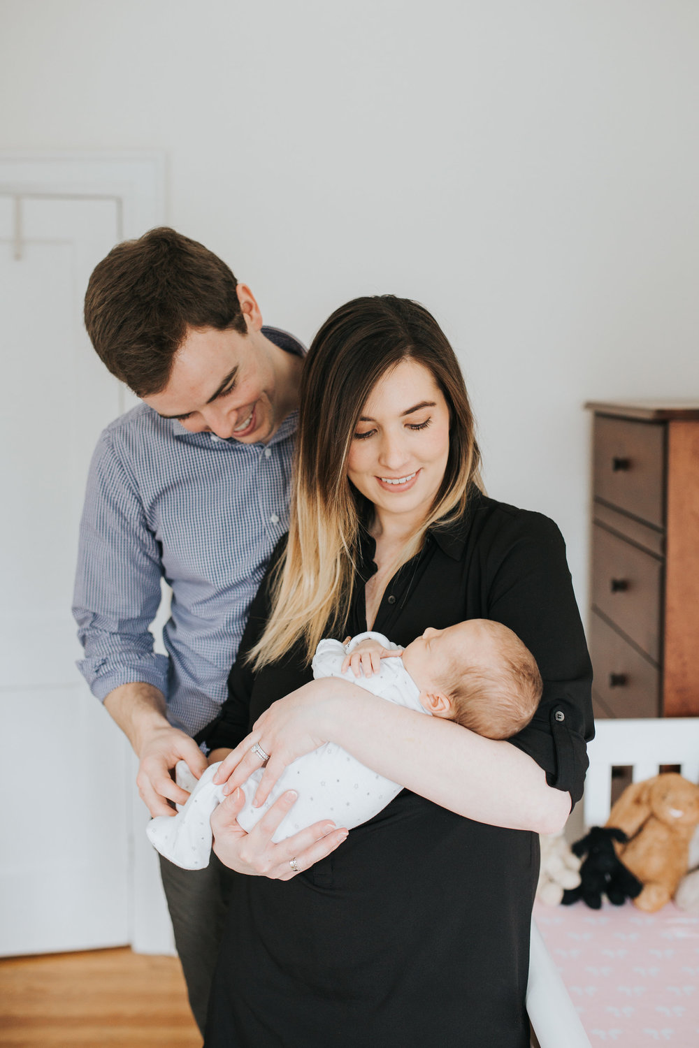 mom holds 4 week old baby girl in nursery, dad stands behind smiling at daughter - Markham Lifestyle Photography