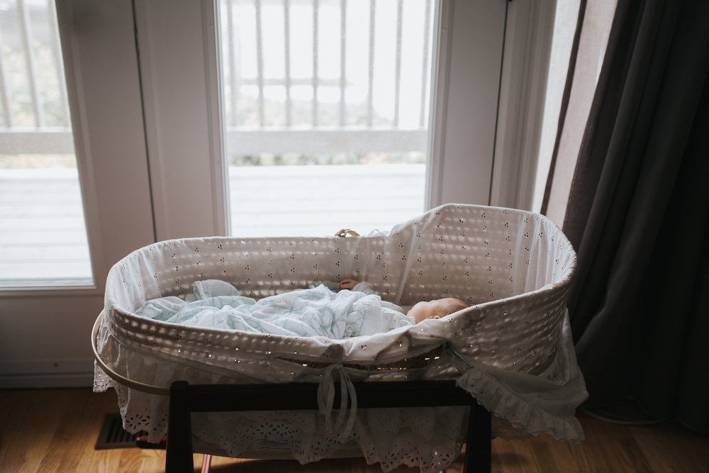 4 week old baby girl sleeping in Moses basket wearing a sleeper and covered in swaddle - Stouffville In-Home Photos