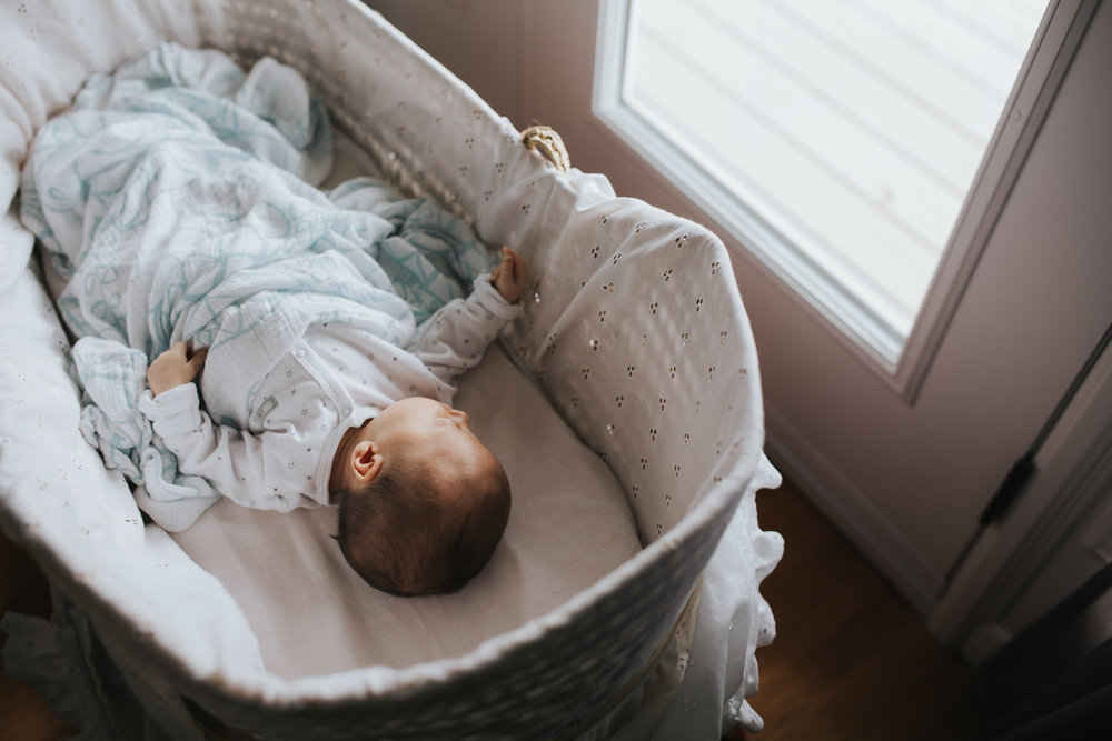 4 week old baby girl sleeping in Moses basket wearing a sleeper and covered in swaddle - Markham In-Home Photos