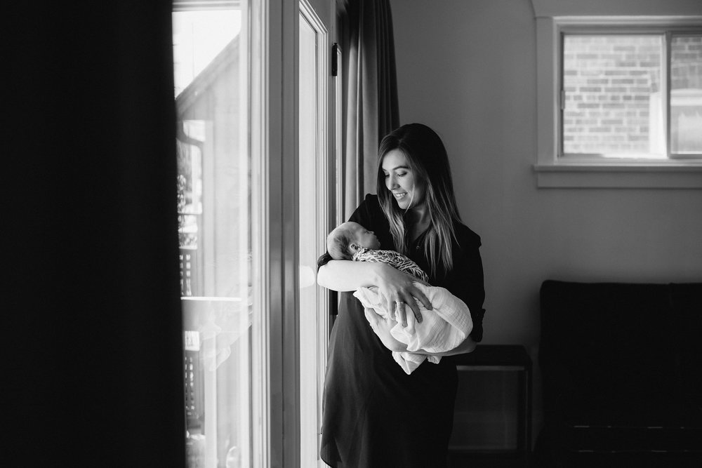 first time mom standing at window holding and looking at 4 week old baby daughter - Newmarket Lifestyle Photos