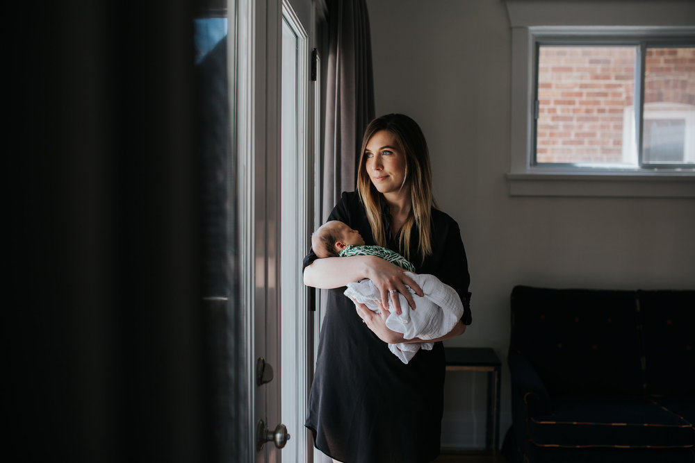 first time mom standing at window holding and looking at 4 week old baby daughter - Stouffville Lifestyle Photos