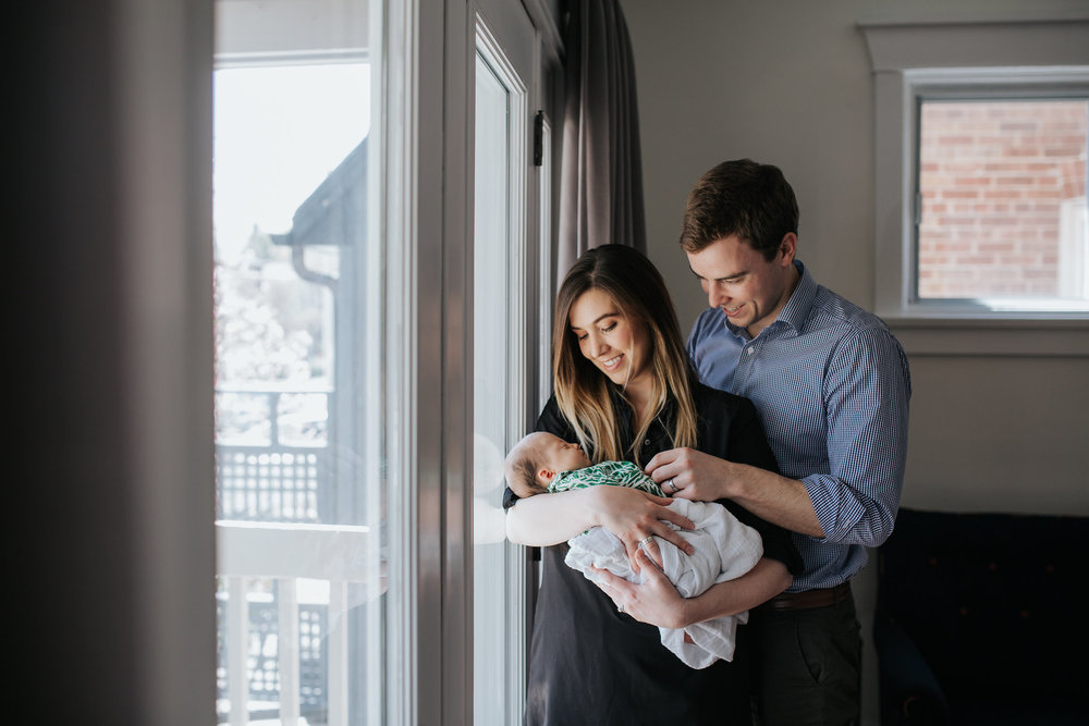 new parents standing at window holding and looking at 4 week old baby girl in swaddle - Barrie Lifestyle Photos