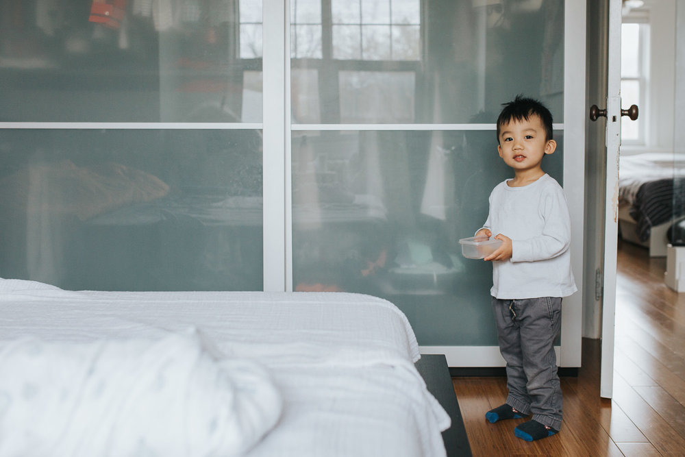 2 year old toddler boy standing with snack in hand, looking at camera - Markham In-Home Photography