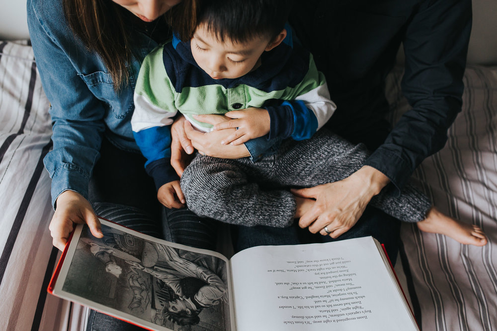 mom and dad sitting on bed reading story to 2 year old toddler son - Barrie Lifestyle Photos