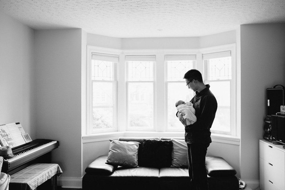 dad stands in living room holding 2 week old baby boy asleep in his arms - Newmarket Lifestyle Photos