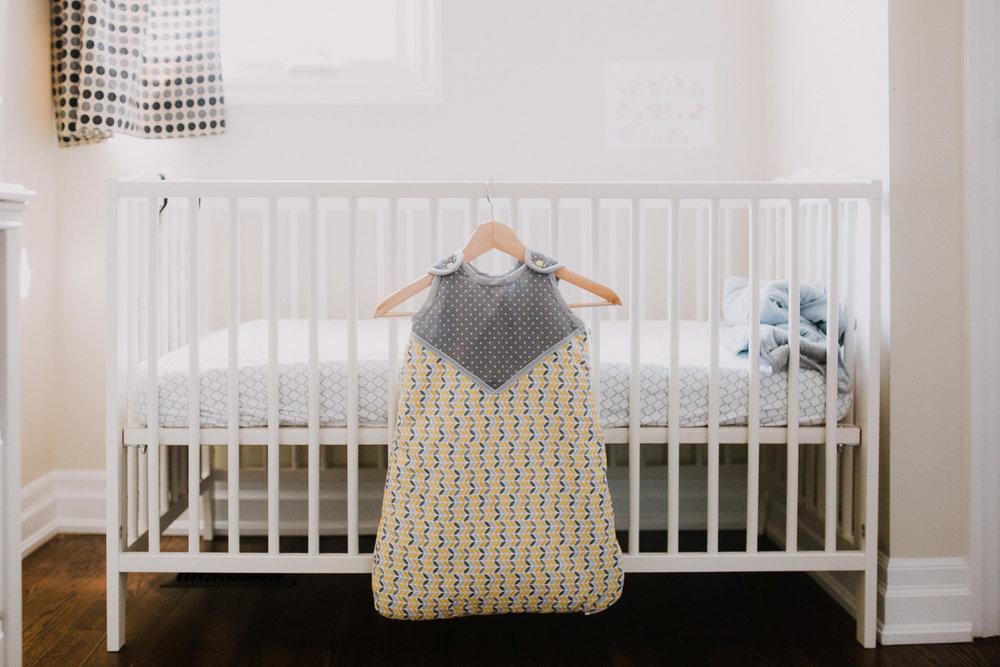 handmade yellow and grey sleep sack hanging on crib in nursery - Markham Lifestyle Photography