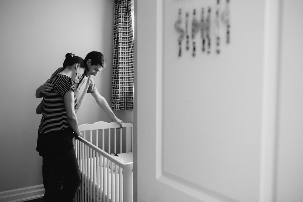 mom and dad standing over crib looking at 2 week old baby daughter sleeping inside - Barrie In-Home Photography