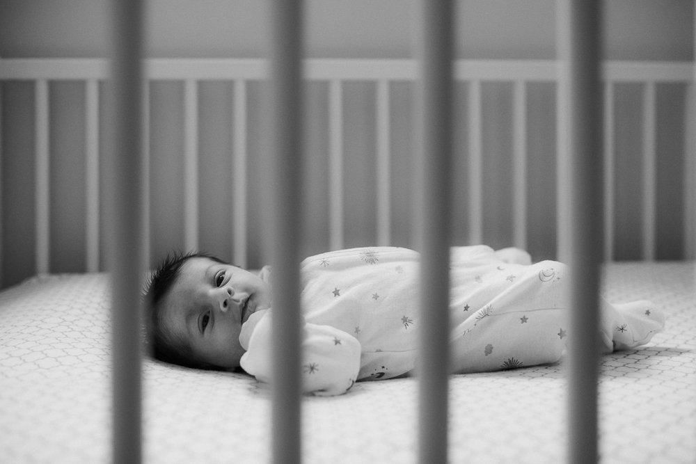 2 week old baby girl in white sleeper lying in crib - Newmarket In-Home Photos