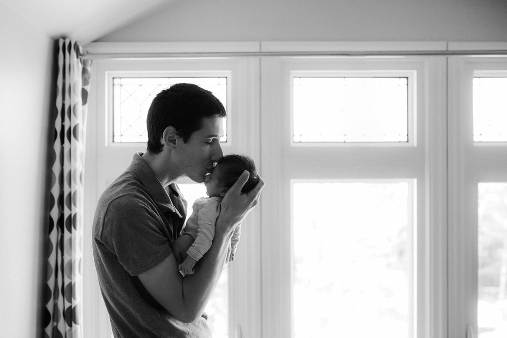 first time dad holding 2 week old baby girl in front of window, kissing her face - Stouffville In-Home Photography