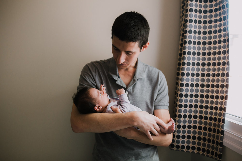 first time dad holding and looking at 2 week old baby girl - Barrie In-Home Photography