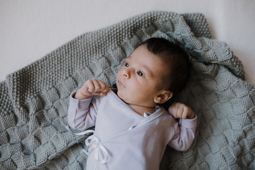 2 week old baby girl in purple onesie lying on hand knitted grey blanket - Barrie In-Home Photography