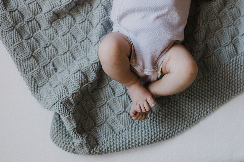 2 week old baby girl in purple onesie lying on hand knitted grey blanket. close up of feet - Newmarket In-Home Photos