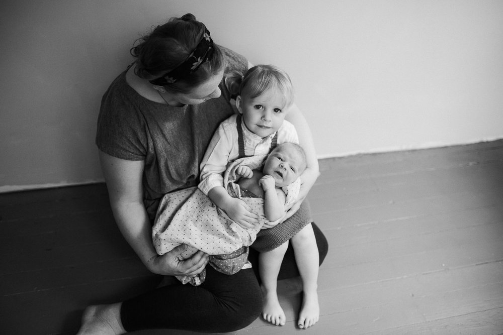 mother sits with toddler daughter and baby son in her arms - Stouffville Lifestyle Family Photography