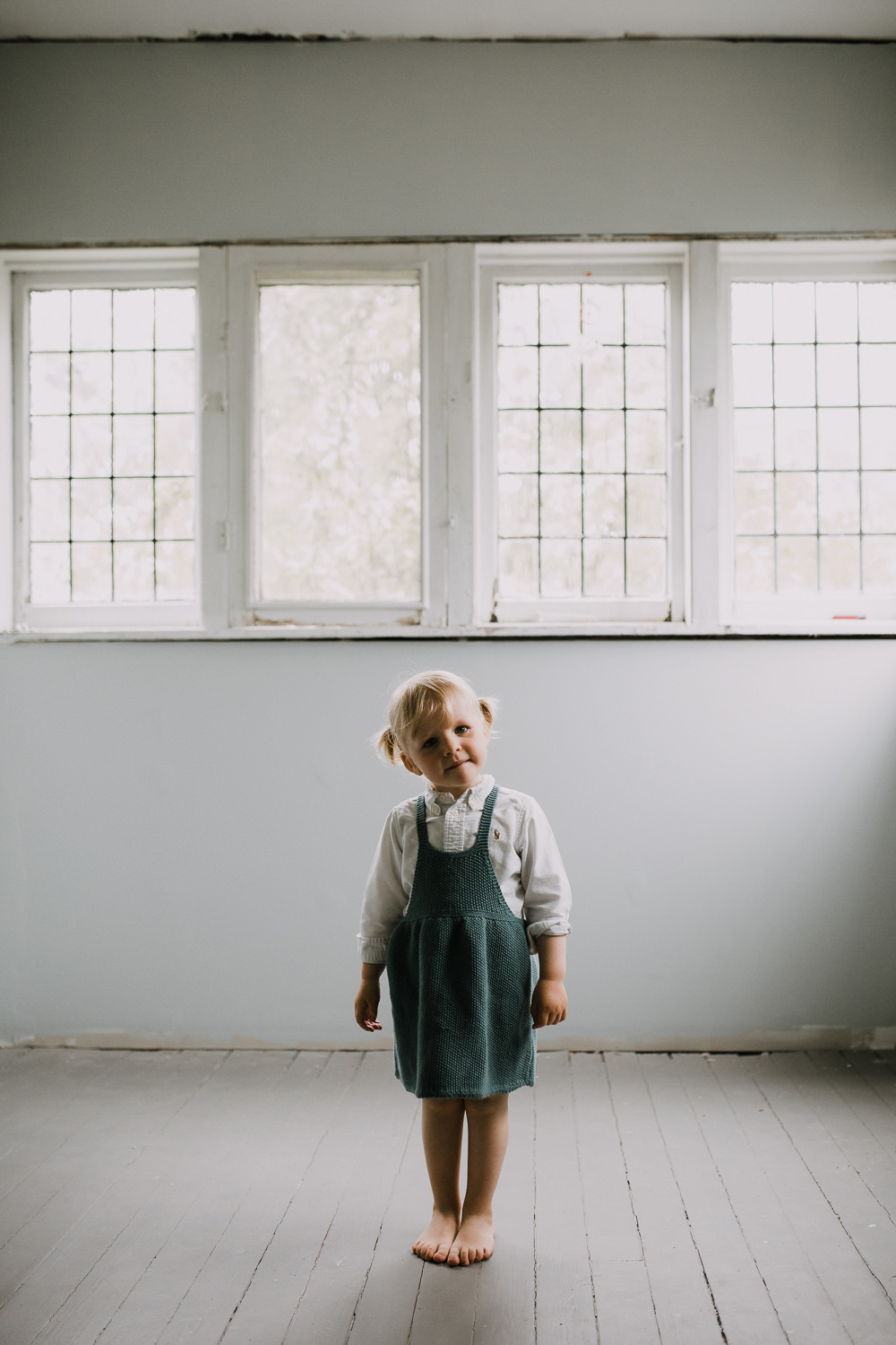 2 year old blonde toddler girl in blue dress stands looking at the camera with head tilted -Barrie Lifestyle Family Photography