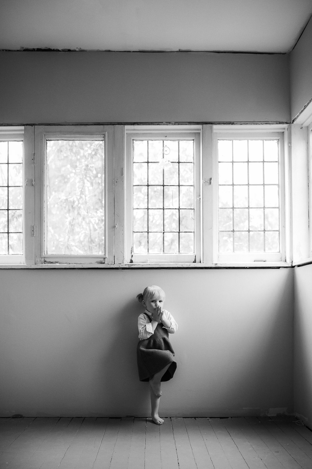 2 year old blonde toddler girl in dress stands leaning against wall practicing yoga tree pose -Newmarket In-Home Family Photography