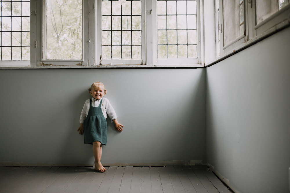 2 year old blonde toddler girl in blue dress stands leaning against wall and smiling at camera -Stouffville In-Home Family Photography