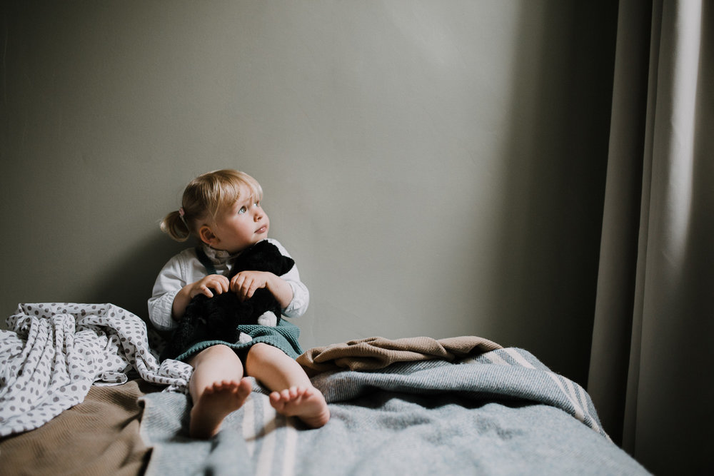 2 year old blonde toddler girl sits on bed holding stuffed cat and looking out bedroom window - Barrie In-Home Family Photography