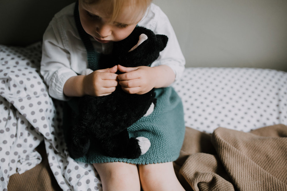 2 year old blonde toddler girl sits on bed hugging stuffed cat - Stouffville In-Home Family Photos