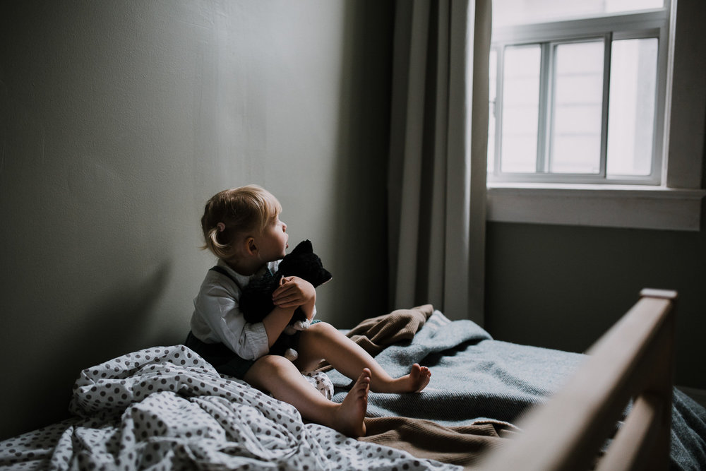 2 year old blonde toddler girl sits on bed holding stuffed cat and looking out bedroom window - Markham In-Home Family Photography