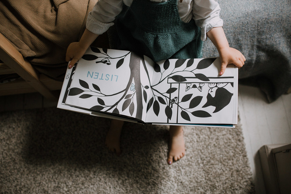 2 year old toddler girl sits on bed with book open on lap - Markham In-Home Family Photos