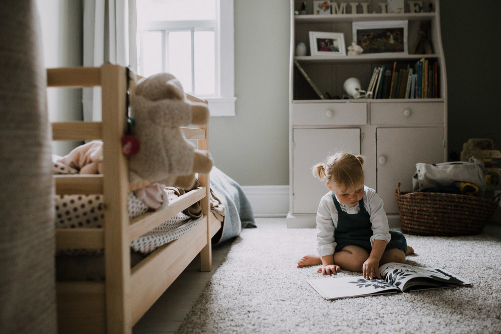 2 year old toddler girl sitting on bedroom floor reading a story book - Barrie In-Home Family Photos