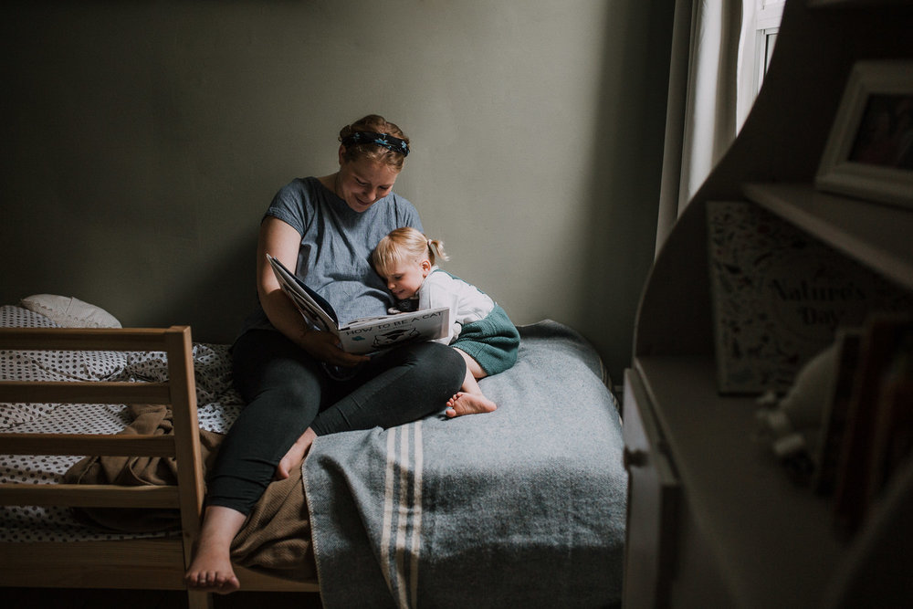 2 year old toddler girl sits on bed with mom, giving her a kiss on the cheek - Newmarket Lifestyle Family Photos