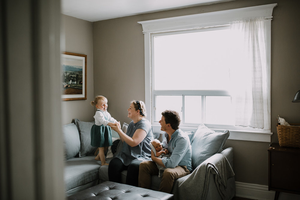 family of four on couch, dad hold 10 day old baby boy while 2 year old toddler girl stands on couch - Stouffville Lifestyle Family Photos