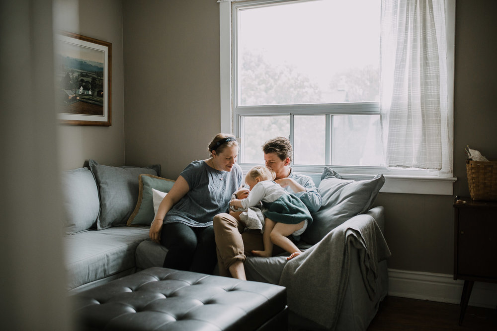 family of four sitting on couch, 2 year old toddler girl kissing 10 day old baby brother - Markham Lifestyle Family Photos