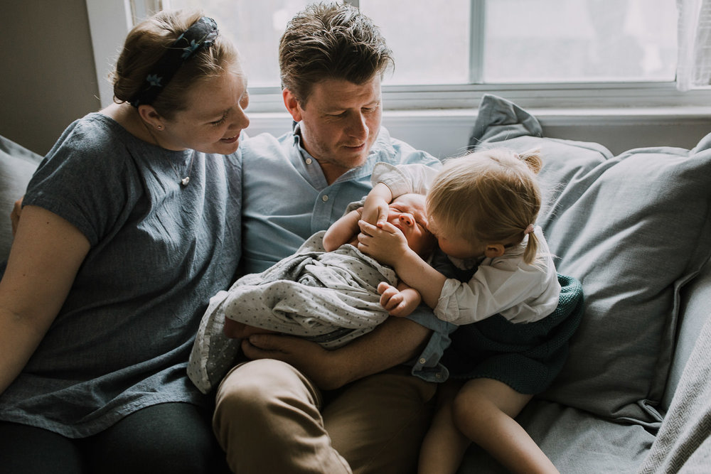 family of four sitting on couch, 2 year old toddler girl kissing 10 day old baby brother - Barrie Lifestyle Family Photos