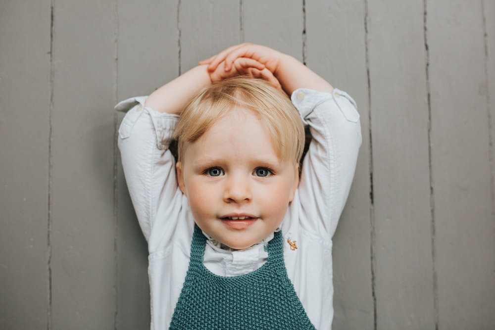 2 year old toddler girl with blonde hair and blue eyes lying on floor looking at camera - Barrie Lifestyle Family Photography