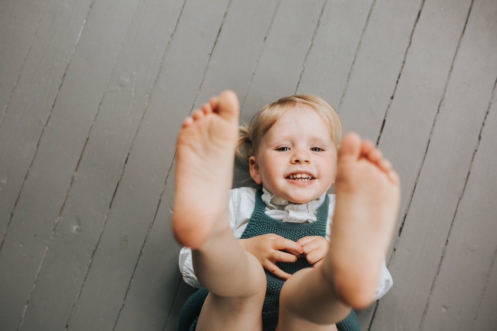 2 year old toddler girl with blonde hair and blue eyes lying on floor looking at camera with feet in the air - Newmarket In-Home Family Photography