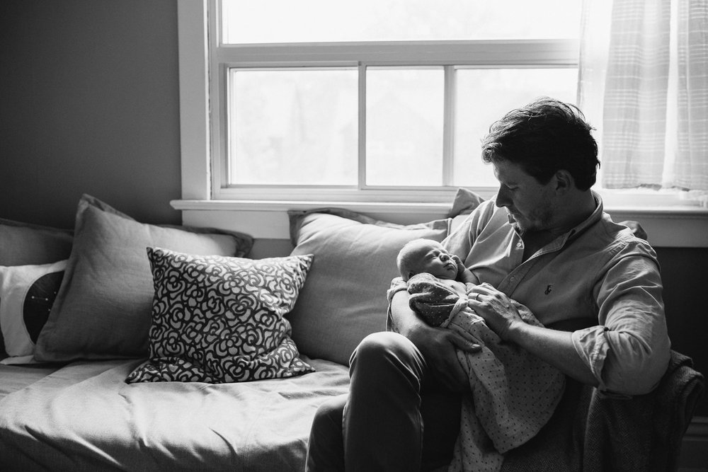 father sits on couch holding sleeping 10 day old baby boy - Markham Lifestyle Family Photos