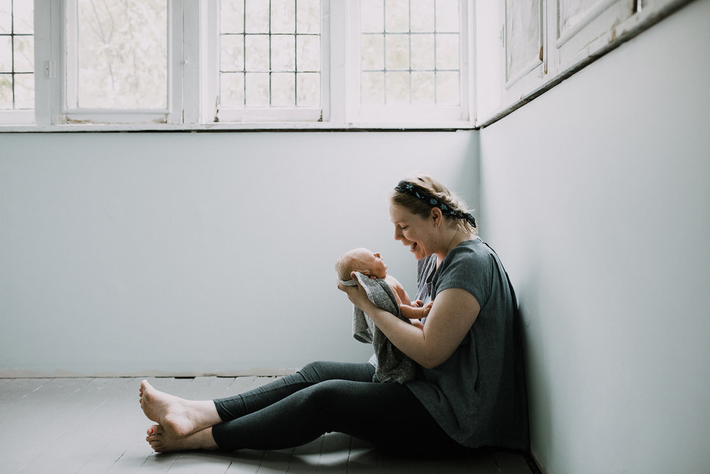 mom sitting on floor looking at 10 day old baby boy in her arms - Newmarket Lifestyle Family Photography