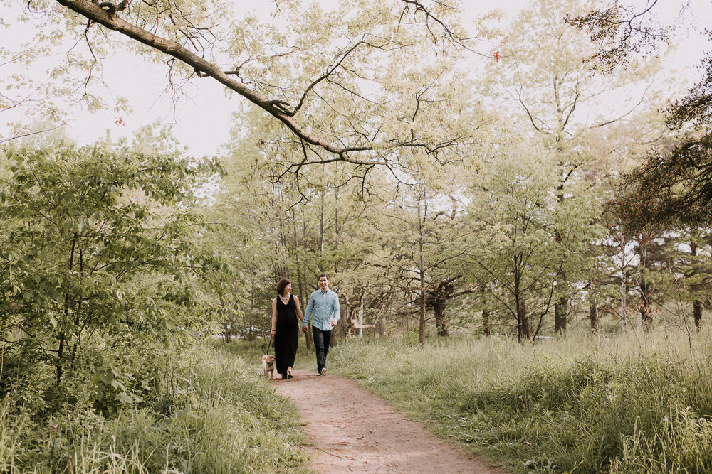 pregnant wife and husband holding hands and walking down forest path with small dog -  Stouffville Lifestyle Photography