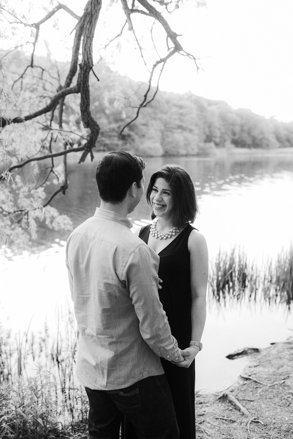 man and pregnant woman standing face to face beside pond, husband holding wife's hand - Barrie Lifestyle Photography