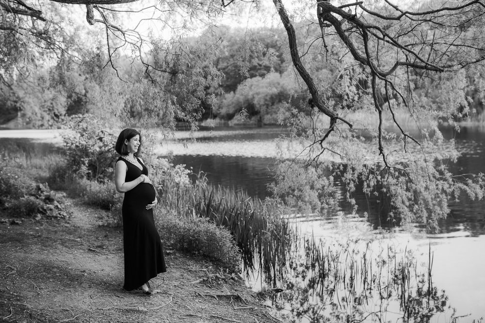 pregnant brunette woman in black dress stands beside river holding baby bump - Stouffville Lifestyle Photography