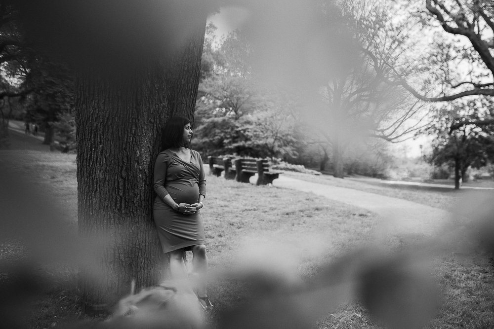 pregnant woman leans against tree while holding baby bump - Newmarket Lifestyle Photography