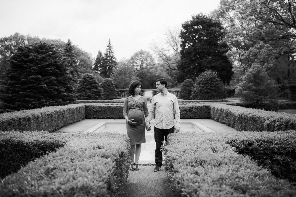 husband and pregnant wife stand holding hands and looking seriously at one another - Barrie Lifestyle Photography